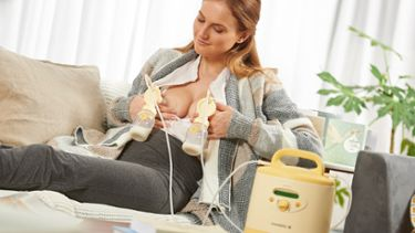 A mother who has a Medela breast pump rental using a PersonalFit™ PLUS reusable rental pump set for Symphony® at home.